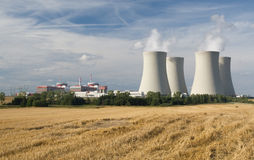 Nuclear power station. Temelin, Czech Republic - power lines and cooling towers, containment buildings, stubble-field in foreground Royalty Free Stock Image
