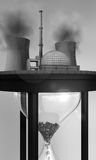 Nuclear power station on huge hourglass. Close-up view of nuclear power station on huge hourglass with atomic waste inside, political caricature of nuclear power Royalty Free Stock Image