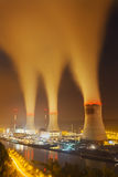 Nuclear Power Station At Night. A large nuclear power station by a river at night with lots of steam Royalty Free Stock Image