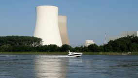 Nuclear power station at river. The nuclear power station of Philippsburg, Germany, as seen from the west over the river Rhine. Closely composed shot including stock video footage