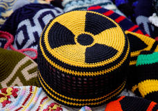 Nuclear radiation hazard sign on knitted hat. Nuclear energy radiation hazard yellow black symbol pattern on knitted fabric cap stock images