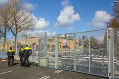 Nuclear Security Summit 2014. The Hague, Holland - March 23, 2014: Group of unidentified policemen watch the entrance to President Kennedy street with big fence Royalty Free Stock Photo