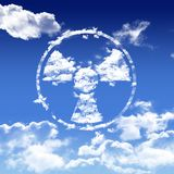 Nuclear symbol is in the air. Nuclear symbol with clouds floating on blue sky beautiful gradiant background Royalty Free Stock Photos