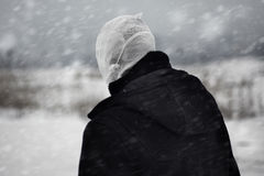 Nuclear winter. Rear view on the human with bandaged head under the nuclear snowstorm Stock Photography