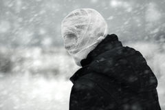 Nuclear winter. Anonymous person with bandaged head under the nuclear snowstorm Royalty Free Stock Photos