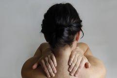 Nude γυναίκα με τον πόνο στην πλάτη σε ένα γκρίζο υπόβαθρο Στοκ Εικόνα