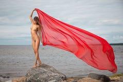 Nude γυναίκα με το κόκκινο ύφασμα Στοκ Εικόνες