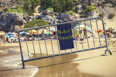 Nude beach sign 3. Nude beach sign with blurred nudist on beach in background. Vintage style Royalty Free Stock Photo