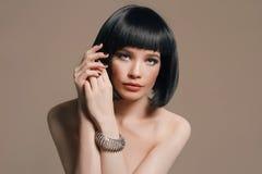 Nude beautiful woman in jewelry. Studio fashion portrait of nude beautiful woman in jewelry. Girl with bob hairstyle Stock Photo