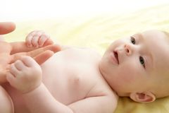 Nude blond baby playing mother hands Stock Photo