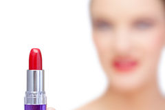 Nude blonde model holding red lipstick on foreground Royalty Free Stock Image