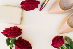 Nude colored high heels still life. Nude colored high heels with lipstick, red roses and wallet hero header Royalty Free Stock Image