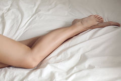 Nude female legs young girl lying in a white bed. In the daylight Stock Photo