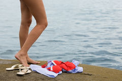 Nude foot girl. Nude young woman is going to swim the sea. Swimsuit and dress the stone Stock Photography