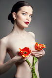 Nude Naked girl with tulips flowers in hand and perfect skin, sexy naked brunette woman to gray background. Skin care of face Stock Images