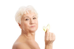 Nude old holding a piece of an apple. Royalty Free Stock Photos