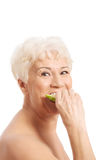Nude old woman eating an apple. Royalty Free Stock Photo