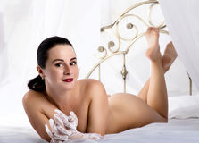 Nude sensual woman in lacy gloves lying on a bed and posing in bedroom Royalty Free Stock Photo