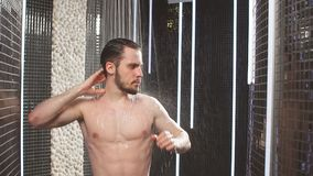 Nude nice man under the contrast shower. Slow motion