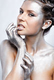 Nude silver girl. Portrait of nude girl body painted with silver posing on gray Royalty Free Stock Photography