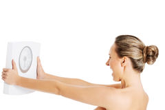 Nude topless woman holding scale. Stock Image
