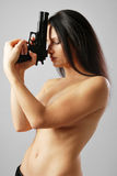 Nude woman with handgun. Nude woman is clasping a gun both hands to her face. Her eyes are closed stock images