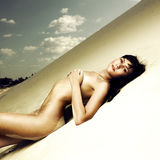 Nude woman laying on sand Stock Photo