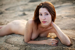 Nude woman laying on the sand Royalty Free Stock Photos