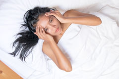 Nude woman lying under a white duvet. And touches the forehead, the view from the top. Stressed Asian girls lying on her back and suffering from a headache Stock Images
