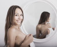 Nude woman with mirror in bedroom Stock Images