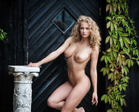 Nude woman posing near the old country house Stock Photos