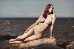 Nude woman posing on sea beach Royalty Free Stock Photo