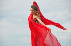 Nude woman with red fabric. Beautiful nude woman with red fabric posing on sea beach against sky background stock photos