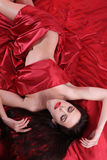 Nude woman on red satin covered herself bed sheets Royalty Free Stock Images