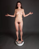 Nude woman on scale Royalty Free Stock Photo
