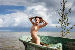 Nude woman sitting in a boat Stock Photos