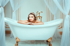 Nude woman sitting in expensive jewelry bath. Crown on his head, his face bright trendy makeup Stock Image