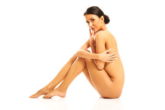Nude woman sitting with knees close to the chest Royalty Free Stock Image