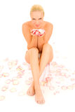 Nude woman sitting between rose. Petals stock photography