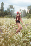 Nude woman standing in a field of flowers. Royalty Free Stock Photography