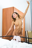 Nude woman stretching in bedroom Royalty Free Stock Photo