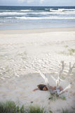 Nude young lady sleeping in sand on the beach stock photo