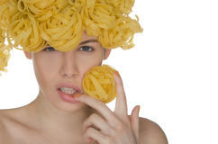 Nude young woman with curls of pasta Stock Image