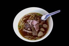 Nudel mit Fleischklöschen und Fleisch auf dem weißen Schlag auf schwarzem Hintergrund Stockbilder