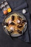 Nudel mit Krake, Miesmuscheln und Tomatensauce auf dunklem Hintergrund stockbild