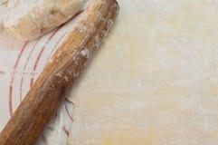 Nudelholz, das auf den rohen selbst gemachten Weizenteig für Teigwaren legt stockbild