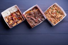 Nudeln mit Schweinefleisch und Gemüse im zum Mitnehmen Kasten auf Holztisch stockfotografie