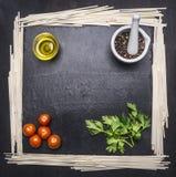 Nudeln mit Tomaten und Orangen auf Schneidebrett mit Kräutern, Rahmenraum für Text Stockbild