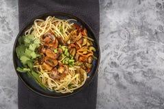 Nudelnudlar för traditionell kines med stekt kött och sallad i en porslinplatta på en grå tabell royaltyfria foton