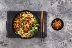 Nudelnudlar för traditionell kines med stekt kött och sallad i en porslinplatta på en grå tabell arkivfoton